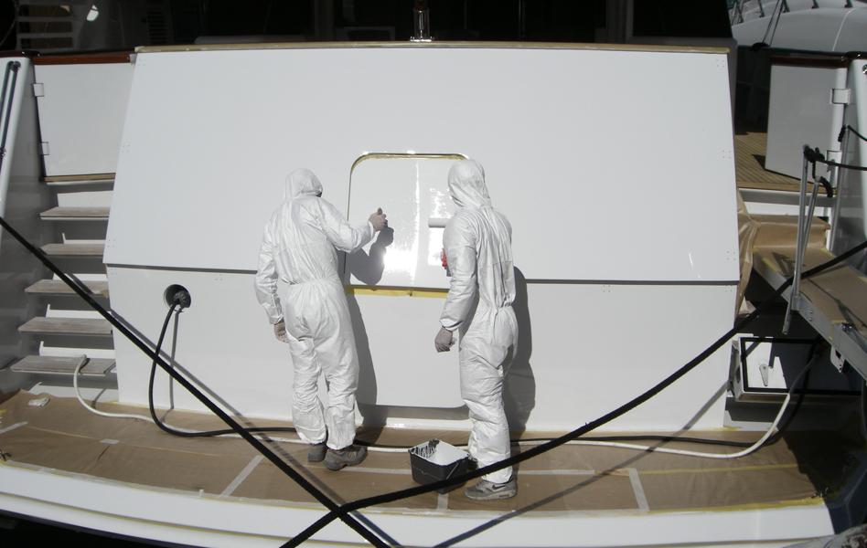 Application à la brosse sur le tableau arrière d'un topcoat  AWLGRIP Matterhorn White. MEFASA 34M. Intervention à flot  à Antibes.